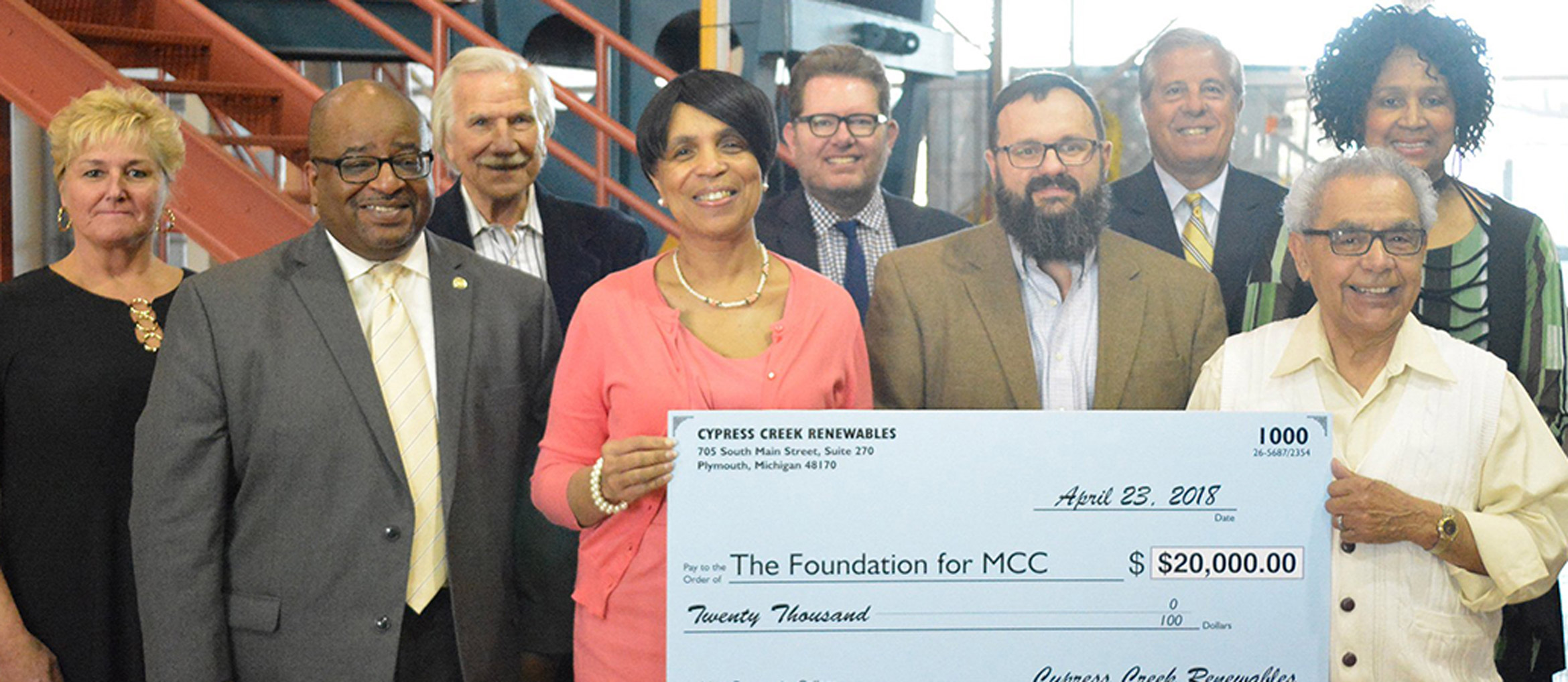 Group of men and women pose with large check at college partnership announcement