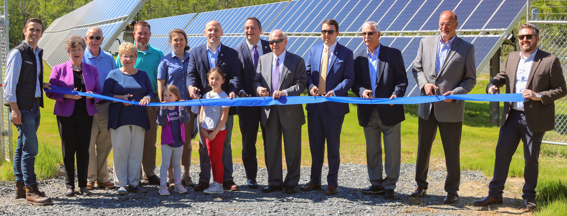 Group cuts ribbon in front of solar panels