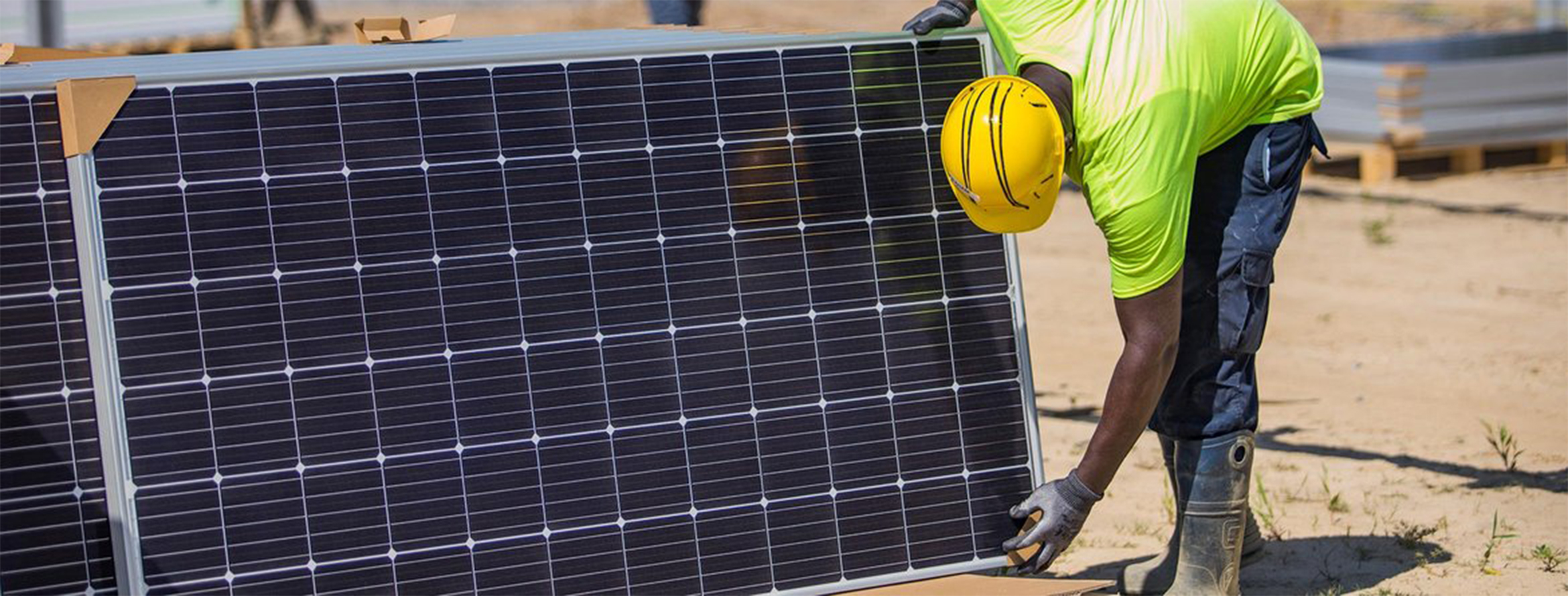 Construction worker in hard hat picking up solar panel on a site