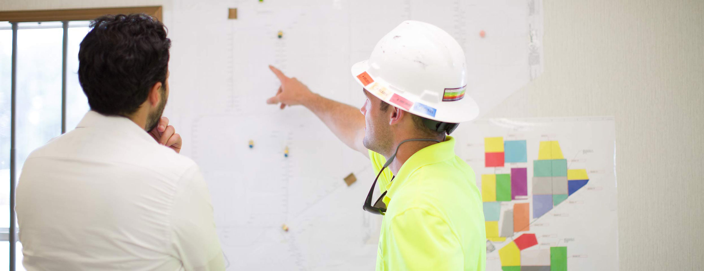 Two employees looking at plans on a wall